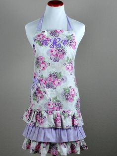 """Vintage Inspired Purple Gingham and Pink Hostess Apron This plum and pink vintage inspired hostess apron will be a sure hit with your guests. Flirty and fun in nature, this stylish apron will make you look fabulous while serving your guests. A must have if you want that special vintage look!The apron is made of 100% cotton and measures 10"""" from neck to waist, 20"""" from front waist to bottom, 21"""" across the waistband   2 ties on both sides.Very lovely and perfect for a ladies tea party and…"""