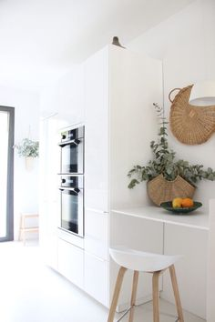 A glossy white storage wall with wall ovens and breakfast nook in designer Ilaria Fatone's kitchen in France
