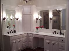 Custom built home - Master Bathroom with custom white cabinets. Corner Linen Tower. Beautiful trim on mirrors oil rubbed bronze wall sconces. Vanity has make up area. Visit us at stevecoxinc.net
