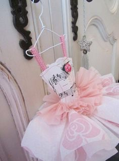 This adorable ballet style dress miniature is made from music sheet, serviette and crêpe  paper.  It is carefully stitched in pink cotton, and has fancy pink trim for shoulder straps with with a paper rose glued in place on the bodice.