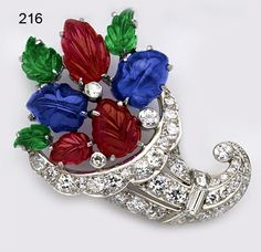 """Art Deco Carved ruby, emerald, and sapphire, baguette diamond, diamond and platinum """"fruit salad"""" cornucopia brooch. French."""