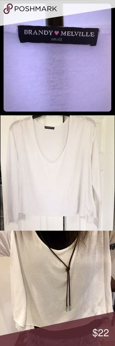 Long-Sleeved,Asymmetrical,Shirt by Brandy Melville Bought ab 6months ago at The Brandy Melville Store in NYC, This Soft, White, Long Sleeved, Scoop-Neck, Shirt is Super Flattering, Stylish & Versatile. Says Size Small (pic#:1) but due 2its Loose/Flowy Fit, it'll Def. Fit sizes XS-M. As seen in (pic#:4)-Theres an Extra, Triangular bit of Fabric on Each Side,Causing Sides 2Hang Longer than Rest of Top, Resulting in an Asymmetrical Look-Tried 2Capture in (pic#3).Only Worn 1-2xs-Great Condition…