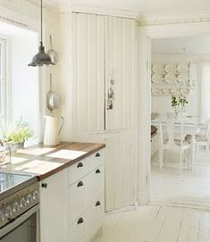 Cottage kitchen: butcher block, cabinet hardware, white wood floors!