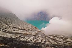 Mount Ijen's crater lake peeking out from behind the clouds of sulphur. Backpacker, travel, gapyear, adventure Indonesia.