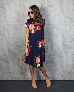 Our Rosemary Floral Dress is perfect for your work or weekend festivities! It's navy base is complemented by red and pink rosettes throughout. The high neck and