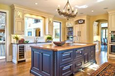 An open concept design and a pass through window make this traditional kitchen easily accessible to the rest of the home. Creams and pale yellows create a friendly, welcoming mood with the chandelier bringing in a touch of elegance.