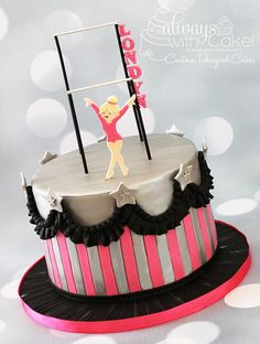 Fun cake with ruffles and stars, for a budding little gymnast. Uneven bars are made with painted skewers. Little girl hand cut out of gumpaste.