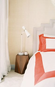 A geometric table topped with a modern lamp adds high-contrast impact in a trad bedroom.