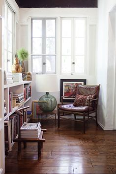 Kimberly Genevieve.  Luv this nook with the low shelves, luv the art, the oversized lamp on the undersized side table, and the worn leather chair and pillow.  And the floors and windows.  Guess I want to live here.