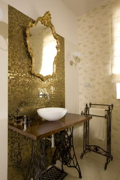 gold bathroom with mirror in gold antique frame and sink table with vintage Singer machine's stand, Harlequin arboreta wallpaper, wallpaper in bathroom, black stylish armchair, armchair in bathroom, gold mosaic Dune