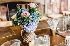 Jugs of hydrangeas and roses -   Image by Kerry Diamond Photography - Bride wears Bespoke Gown & Veil by Dana Bolton. Outdoor Ceremony at Voewood House in Norfolk with Picnic Wedding Breakfast & Lawn Games.