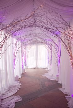 Wedding guests walked beneath a canopy of tangled branches entwined with twinkling lights and purple uplighting before entering the ceremony space. #InsideWeddings #Draping #CeremonyDecor Photography: Aaron Delesie Photographer Read More: http://www.insideweddings.com/weddings/snowy-spring-celebration-in-aspen-colorado/596/
