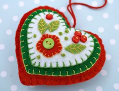 Handmade felt heart ornament with layers of applique and embroidery in green, red and white, embellished with tiny buttons. A special handmade felt Christmas ornament. x x 3 inches approx, with a cotton loop for hanging. Cat Christmas Ornaments, Felt Christmas Decorations, Christmas Hearts, Felt Ornaments, How To Make Ornaments, Handmade Ornaments, Handmade Felt, Handmade Christmas, Felt Embroidery