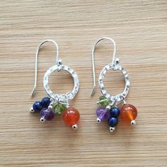 "Hammered sterling silver circles swing above gemstones wire-wrapped by hand. The bright mix of blue lapis lazuli, purple amethyst, orange carnelian, and green peridot is truly festive. The earrings are 1"" in length and hang from sterling silver ear wires. Check out more"