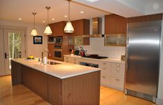 Projeto de cozinha moderna com detalhes em madeira e geladeira em inox