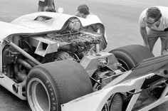 "This Karl Ludvigsen photo shows the open engine compartment of the Chaparral 2H as it appeared at Mid-Ohio in 1969. The narrow track of the car, combined with enormous tires prevented a normal rear suspension. Likewise, the lack of width required the exhaust to be routed to exist in front of the rear tires. In retrospect, Jim Hall stated that had the car had about a 4"" wider track and a similar increase in wheel base, it may not have had the handling quirks it was plagued with."