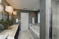The wall-mounted faucets in this contemporary bathroom are perfectly suited to the modern, classic lines of the design.  Large crystal and chrome vanity wall sconces illuminate the space evenly, and add lots of style to the sleek gray space.