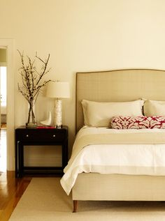Lamp and a vase of twigs plus a neutral, natural headboard... for master