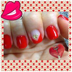 Manicure en rojo con diseño francés y corazon en dorado.