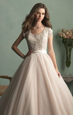 Imagine the radiant bride you will be in Allure Bridals M524. This elegant wedding gown features scallop neckline and cap sleeves. The bodice embellished with shining beads. The full ballgown skirt crest with a train that exudes elegance as you down the aisle.