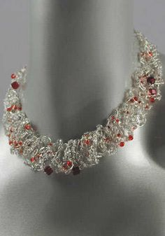 This artistic wire crochet necklace is adorned with red Swarovski crystals