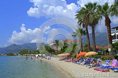 Ionian sea clear water,vacationers relaxing on sunbeds  Nydri  beach and Lefkada island  beautiful landscape,Greece