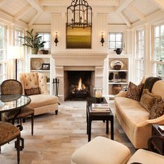 Sunroom after renovation including new vaulted ceiling & limestone fireplace flanked by leaded glass windows