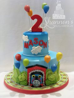 Thomas & Friends 2-tier fondant covered cake with airbrushing and fondant balloon accents. Marble cake with strawberry buttercream filling and chocolate ganache under fondant. Design credit: K Noelle Cakes. Keyword: train, birthday.