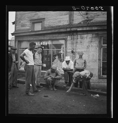 Miners shooting craps in front of company store. Osage, West Virginia Photographer Marion Post Wolcott Created September 1938