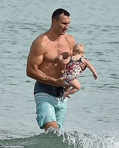 Ripped tide: Wearing just long blue surf trunks, the boxer showed off the flawless physiqu...
