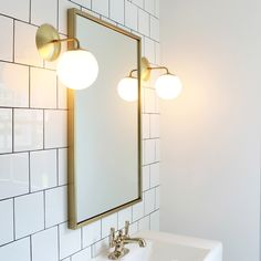 Love this tile going up the wall. Allows the light to shimmer and bounce. Great statement wall for a small bathroom. This is a very inexpensive tile that they offset and added a dark grout to make more modern. - Model Home Interior Design Bathroom Sconces, Bathroom Renos, Small Bathroom, Master Bathroom, Bathroom Lighting, Gold Bathroom, Bathroom Ideas, Brass Bathroom Light Fixtures, Wall Sconces