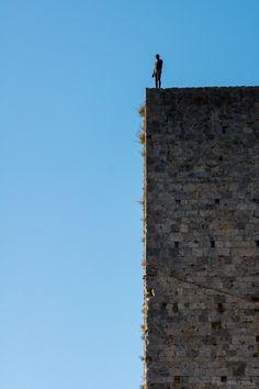 San Gimignano está en lo alto de una colina, y esto permite que se disfrute de vistas de los campos toscanos hasta varios kilómetros de distancia. Si nos subimos a lo alto de alguna de sus torres, las vista ya son más que espectaculares.   Aquí una de las torres de los Salvucci, de las más altas de San Gimignano, con una polémica estatua del escultor londinense Antony Gormley. Y digo polémica porque representa un hombre desnudo con su... esto colgando, y como ésta hay dos más en las calles…