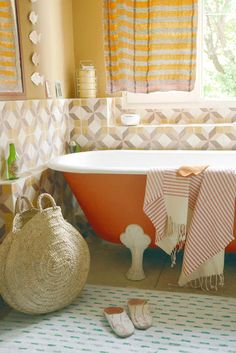 Image above: The bathroom has a Moroccan feel. The curtains and bathmat are from Chez Caravan Chambre 19 in Paris. The small mirrors, basket and slippers were found in the souk in Marrakesh (see more here). The towel was a creation by our collective, Copirates. The tiles that cover the wall behind the bathtub are from an old factory in Villeneuve les Avignon. The bathtub is from the 19th century and was found on the internet and painted bright orange.