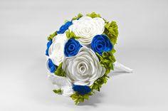 1920 Bouquet. Elaborado con 18 flores en dos tamaños diferentes y entremezcladas con flores naturales preservadas, formando un ramo de cerca de cuarenta centímetros de diámetro. El mango, forrado en lazo de raso blanco y adornado con tres alfileres acabados en perla.