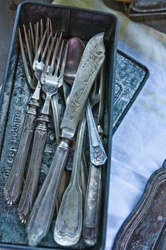 Old mixed flatware in a baking pan