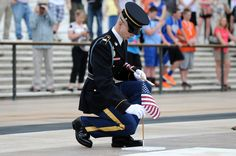 Spc. Seth Wymer, Sentinel, Tomb of the Unknown Soldier, 3d U.S. Infantry Regiment (The Old Guard), places a flag at the foot of one of four crypts of the Unknowns in Arlington National Cemetery, Va., May 23, 2013 The ceremony, known as Flags In, is performed to commemorate and honor U.S. military personnel ahead of Memorial Day weekend and has been conducted annually since 1948. (U.S. Army photo by Staff Sgt. Megan Garcia)