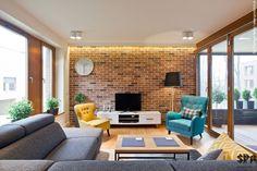 Czerwone cegły na ścianie telewizyjnej przykuwają do siebie uwagę i stanowią wdzięczne tło dla kolorowych foteli i...