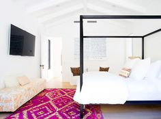 White walls, black bed frame, white bedding, printed pink rug, and printed orange seating