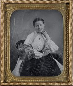 She is wearing a dark apron (dark colors hid dirt) and carries a basket, indicating she is a working woman. She gives a little smile, unusual for 19th-century photographs. Although her bodice has buttons down the front, it probably closes using hooks and eyes.