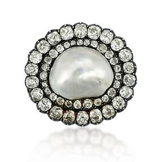 A 19TH CENTURY NATURAL PEARL AND DIAMOND BROOCH The central baroque shaped natural pearl measuring approximately 19.6mm across, to the old-cut cushion shaped diamond double row surround, mounted in silver and gold