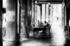 Lunch break - A young man sitting alone at a table in a street cafe in Pisa. The table stands in a colonnade. Impressionist street photography in black and white. #street #streetphotography #pisa #impressionism #blackandwhite #photography