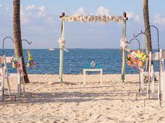 Beach arch white flowers and jar mason decor at Key Largo Lighthouse Beach Wedding Venue in the Florida Keys