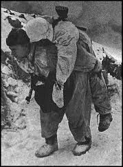 By autumn, Leningrad's connection to the Soviet interior was all but severed. Yet Red Army patrols ventured to the city perimeters, deliberately drawing Axis fire. Here a defender carries his wounded comrade to safety, perilously close to an exploding shell. Finally, in early 1943, the Soviets opened a corridor to the city at a cost of 250,000 casualties. Leningrad took its courageous place in history.