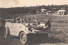 A VW Type 82 Kubelwagen with an officer with his staff appear to be traveling with a column of soldiers
