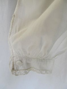 "Mid 19th Century Night Gown: ""The nightgown features a yoked bodice both front and back; the yoke is a double layer of fabric, which adds strength to the shoulders which receive the most wear. There are also reinforcements on the underarms. The front of the yoke and cuffs is trimmed with tucks and white cotton lace. White milk glass buttons the entire front length. Side gussets. All the seams are fully finished, most being flat felled. Measurements: Bust - 50"", Shoulders - 19"", Length…"