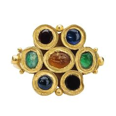 Late Roman Ring, late 4th–5th century, Roman. Made in probably Britain. Gold, set with yellow, green, and red glass, two sapphires, and a garnet. Bezel 28 x 23 x 4 mm.; circumference 58 mm.; weight 10.1gr.