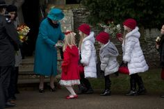 Britain's Queen Elizabeth II receives flowers from children after attending the British royal family's traditional Christmas Day church service in Sandringham, England, Tuesday, Dec. 25, 2012.  (AP Ph