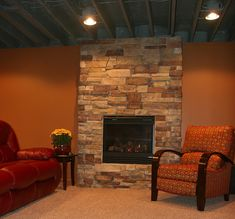 This Basement Features An Exposed Ceiling W/ Can Lights U0026 Beautiful  Fireplace.