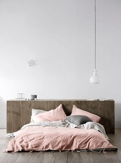 white bedroom with dusty rose bedding, gray pillow, brown wood headboard, platform bed, bare bulb pendant light, dusty pink, dusty rose, rose quartz, pantone pale dogwood