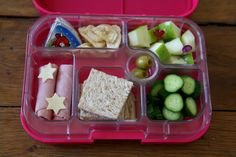 Keep it simple, yet pretty! This Yumbox packed lunch has organic ham, gouda cheese stars, wholewheat bread, persian cucumbers, apple, banana chips and the Laughing Cow cheese.